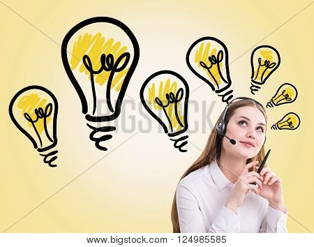 Idea concept with pretty call center operator on yellow background with lightbulbs