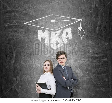 Businessman and businesswoman shoulder to shoulder MBA and academic hat drawn over them. Black background. Concept of education.