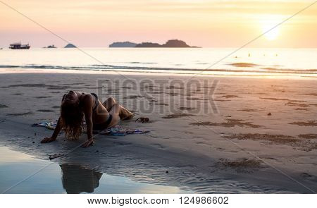 Young woman sitting on the sea beach in the setting sun.