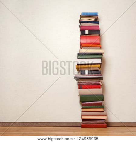 Big stack of old books on wooden floor