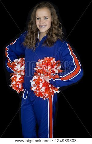 young high school cheerleader standing with pom poms at her hips smiling black background