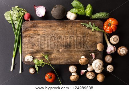 fresh vegetables and ingredients for cooking around vintage cutting board on black background