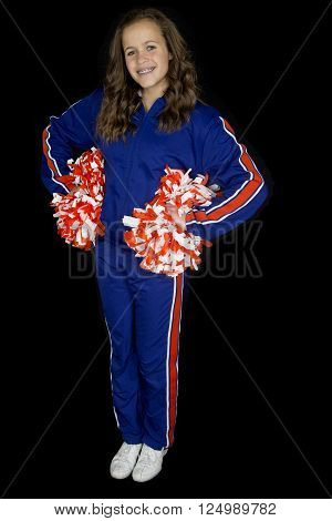 Cute teen cheerleader standing smiling black background