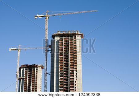 Buildings under construction with cranes against the blue sky.