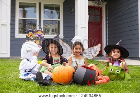 Children Dressed In Trick Or Treating Costumes On Lawn