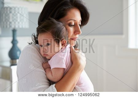 Loving Mother Holding Baby Daughter At Home