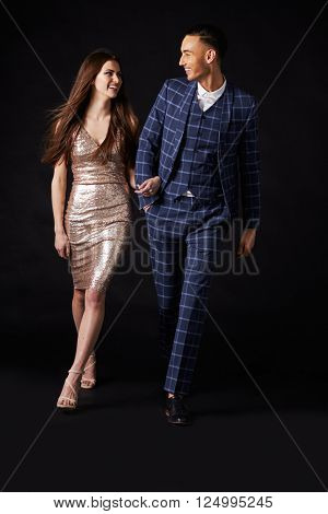 Fashionable young couple walking together arm in arm