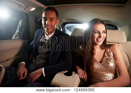 Attractive young couple laughing in the back of a limousine