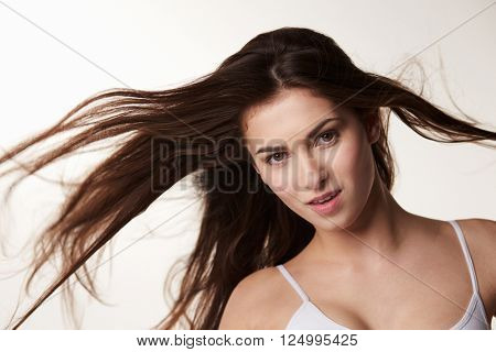 Dark haired, late teen girl with hair blowing, horizontal