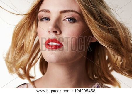 Glamorous blonde woman with hair blowing, looking to camera