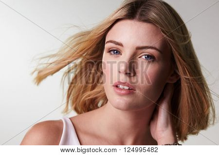 Blonde woman looking at camera, hair blowing, horizontal