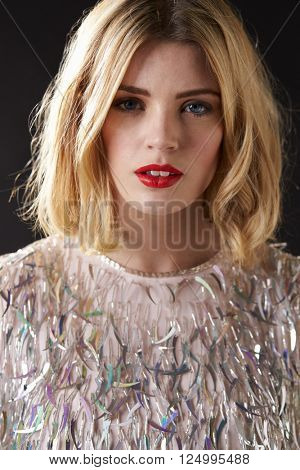 Vertical portrait of glamorous blonde woman in fringed dress