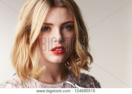 Glamorous blonde woman looks to camera, horizontal portrait