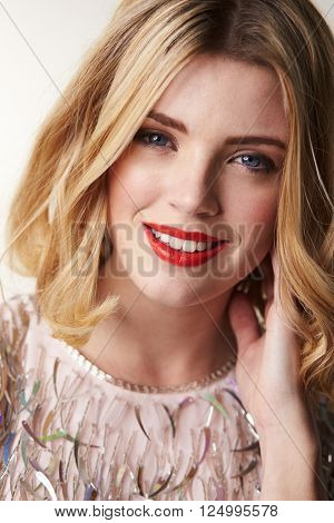 Glamorous blonde woman smiling to camera, vertical portrait