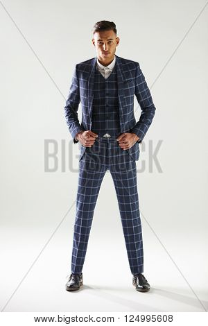 Full length portrait of young man wearing checked suit