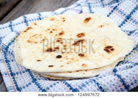fresh Homemade Naan Flatbread pile on table
