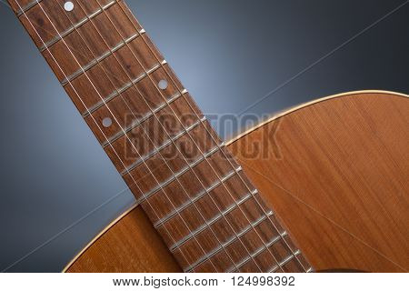 A detail shot of a neck of a western guitarin front of a grey background.