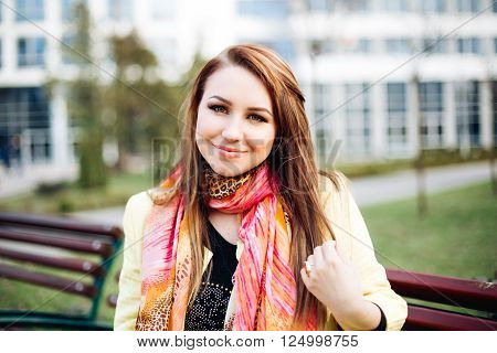 Close-up portrait of an insanely beautiful girl with bright eyes, makeup. The woman is resting, posing for the camera, smiles. Blonde in bright outfit, colorful scarf, yellow coats. Blurring the background