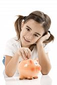 stock photo of piggy_bank  - Little girl lying on floor and inserting a one euro coin on the piggy - JPG