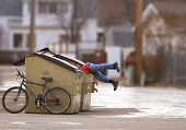 foto of dumpster  - homeless man with a bike looking in a dumpster - JPG