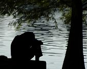 stock photo of sad man  - Silhouette of a depressed man by the lake - JPG