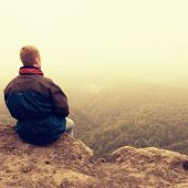 Постер, плакат: Melancholy And Sad Day Man At Enge Of Rock Above Deep Vally Tourist On The Peak Of Sandstone Rock