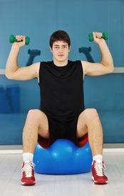 stock photo of lifting weight  - young man in fintess sport club exercise withweights and relaxing - JPG