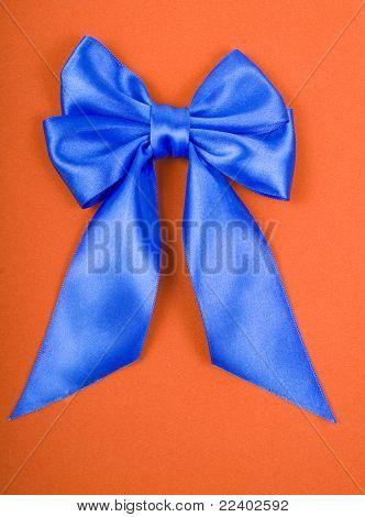 Blue satin bow on orange velvet background