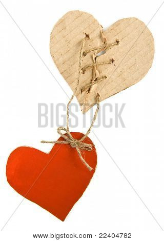 Torn cardboard hearts with rope isolated on white background