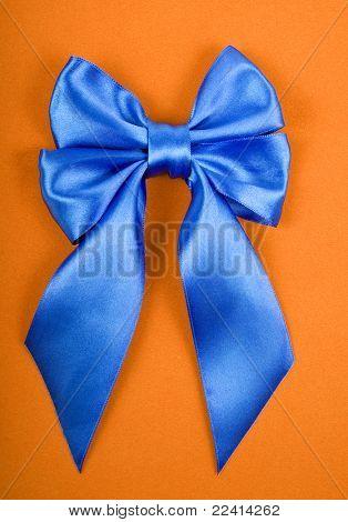 Blue satin bow on yellow velvet background