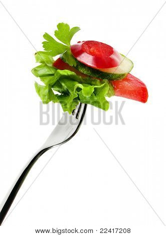 Fork with salad from vegetables isolated on white