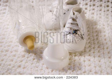 Постер, плакат: Детская обувь и бутылка, холст на подрамнике