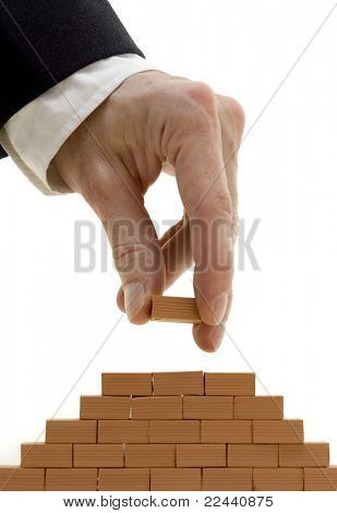 businessman building a bricks wall pyramid isolated on white