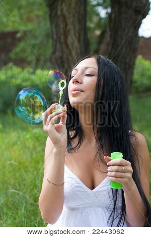 Girl Inflates The Bubbles In The Park