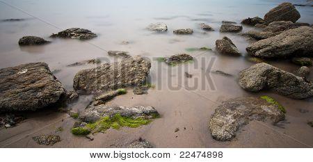 Long Exposure Of Rocks On Wet Sand