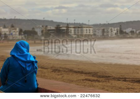 Moroccan Woman In Blue Dress Watching The Beach