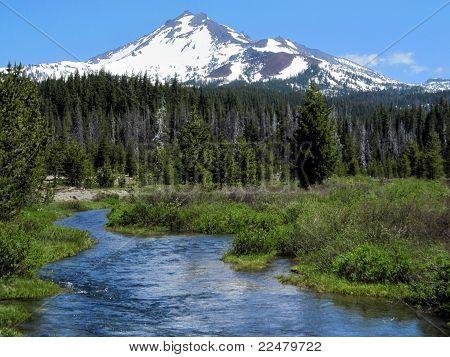 a mountain stream runs off a snow-capped peak