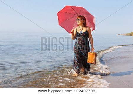 Middle-aged Woman Goes To The Beach With An Umbrella And A Suitcase