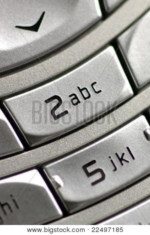 Close-up of phone keypad, emphasizing '2abc' key.