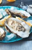 Fresh Oysters close-up on blue plate, served table with oysters, lemon and ice. Healthy sea food. Oy poster