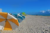 Colorful umbrellas line the beach in Miami Beach, Florida in the South Beach art deco district. poster