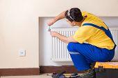 Young repairman contractor repairing heating panel  poster