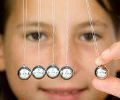 foto of gravity  - young girl holding a pendulum ball - JPG