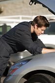 stock photo of car repair shop  - Young mechanic fixing a car - JPG