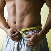 stock photo of tape-measure  - Muscular Young Man with Bare Chest Measuring Waist - JPG