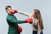 Couple fighting in boxing gloves on light background. Problems in relationship poster