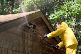 foto of pressure-wash  - a man pressure washing the roof of a garage - JPG