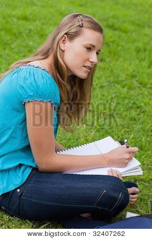 Attractive young girl sitting in the countryside while seriously doing her homework