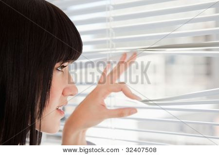 A woman at the window as she looks out through the blinds