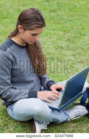 Serious young girl typing on her laptop while sitting cross-legged in a park